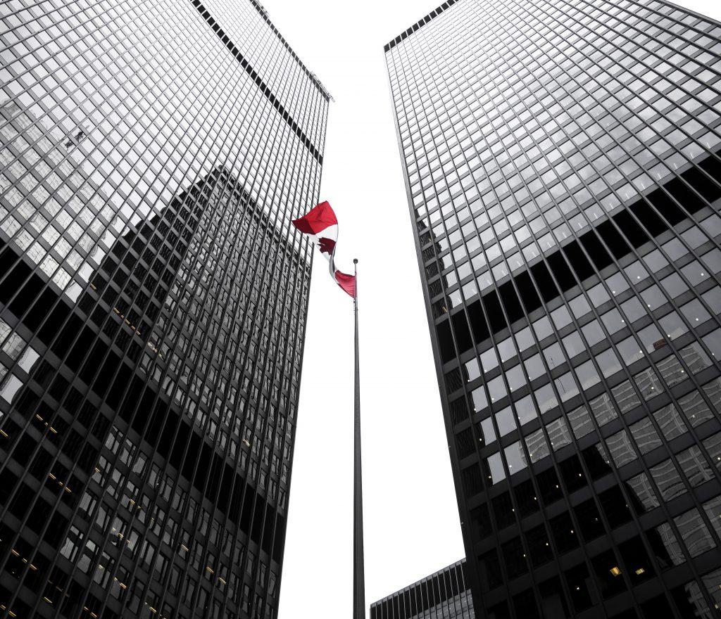 Photographie à faible angle des tours de grande hauteur et le drapeau canadien flottant au milieu