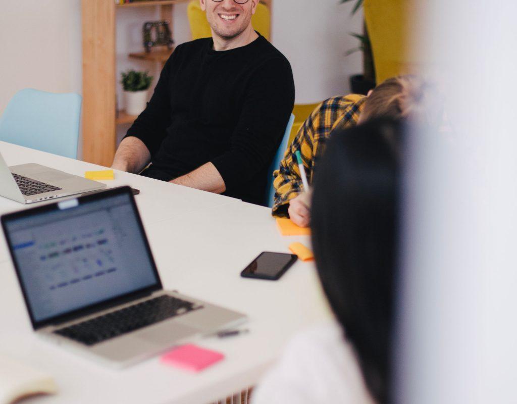 Homme souriant en face d'une personne qui écrit